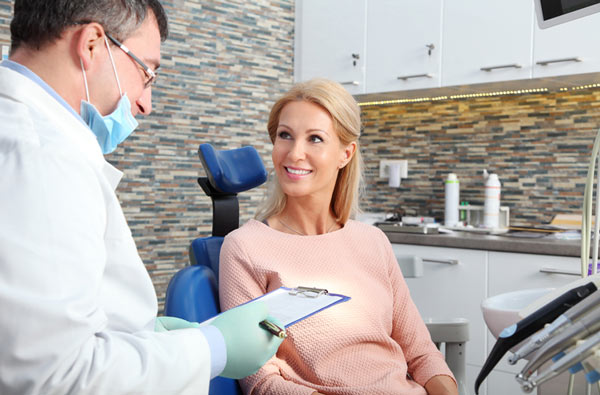 Woman talking to dentist during dental exam at Irvine Dentistry in Irvine, California.